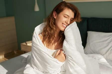 Smiling woman after awakening in bed 免版税图像