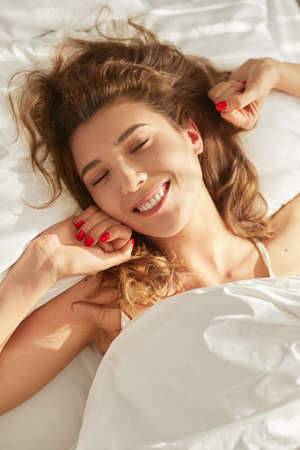 Happy woman lying in bed in morning