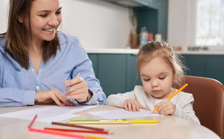 Mother and kid drawing together at home