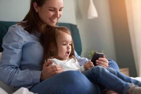 Mother and kid using smartphone together