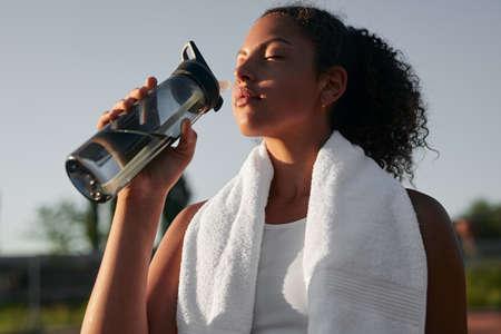 Black sportswoman drinking water during training in summer