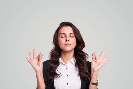 Businesswoman meditating with mudra gesture