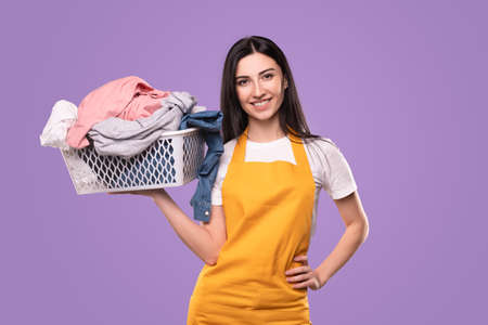 Happy housewife in apron with laundry