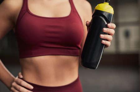 Crop sportswoman with protein in shaker 免版税图像
