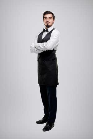 Confident waiter in elegant uniform