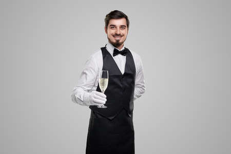 Smiling waiter with glass of champagne