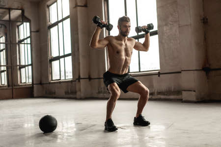 Muscular man doing weight exercise with dumbbells