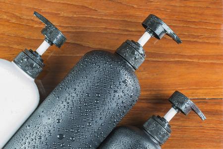 jabon liquido: Botella de jabón líquido, gel de ducha, champú, sobre fondos de madera.