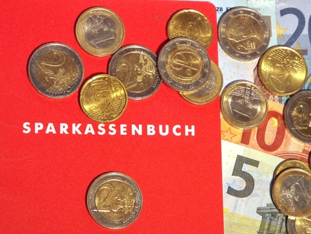 passbook: Passbook.  Some Euro notes and coins lying on a German deposits book.