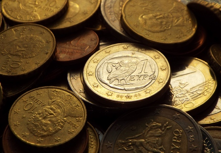 greek coins: Greek euro in the dark -  The Greek 1 euro coin is lying on a pile of coins.