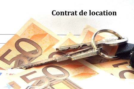 Rental agreement: Key to money - Apartment keys lying together with some 50 euro bills on a lease form.
