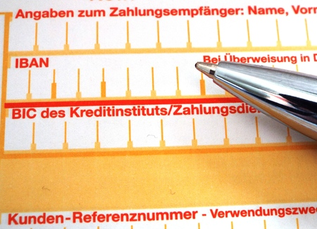 IBAN - Close-up of the IBAN and BIC fields of a transaction form, along with the tip of a pen.