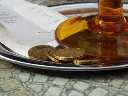 Tipping on a tray located under a brown glass a receipt alongwith loose change. Standard-Bild
