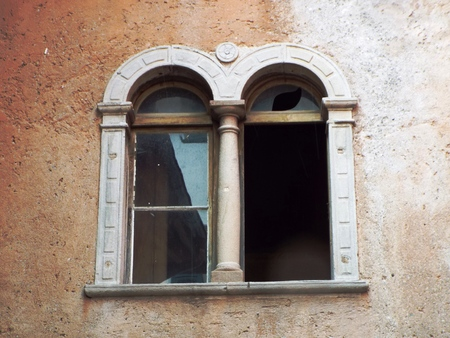 old windows: Old windows - Old windows with broken panes, two-part window with arches, in a yellowish-brown wall.