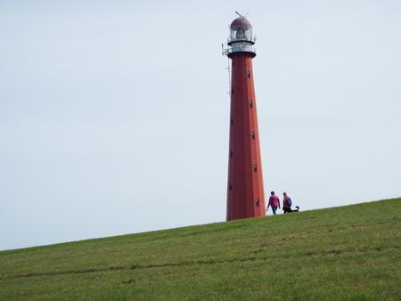 den: Lighthouse behind the dike - Behind a green dike stands a red lighthouse in the light blue sky. Den Helder 09.09.2105 Editorial