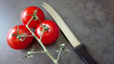 Vine-ripened tomatoes - Three ripe vine tomatoes are resting at on inflorescence. Next to it is a tomato knife.