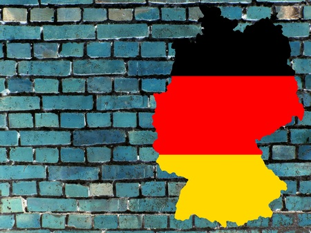 German policy (Topics Background) - The map of Germany in the colors of the national flag in front of a bluish brick wall