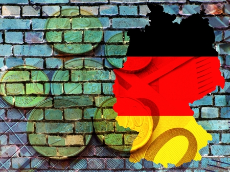 German financial policy - The map of Germany in the colors of the national flag in front of a bluish brick wall. Translucent: Euro coins.