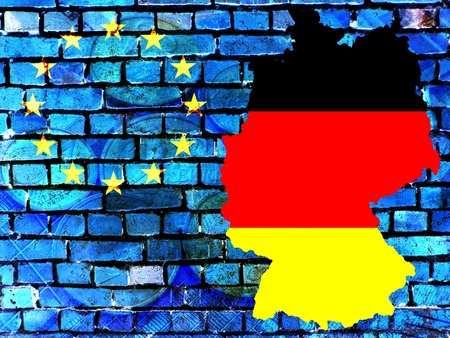 The map of Germany in the colors of the national flag in front of a bluish brick wall with the European circle of stars. Translucent: Euro coins. Stock Photo