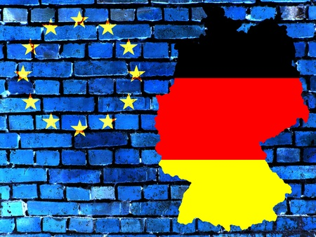 The map of Germany in the colors of the national flag in front of a bluish brick wall with the European circle of stars. Standard-Bild