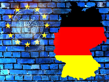 The map of Germany in the colors of the national flag in front of a bluish brick wall with the European circle of stars. Translucent: a Euro coin.