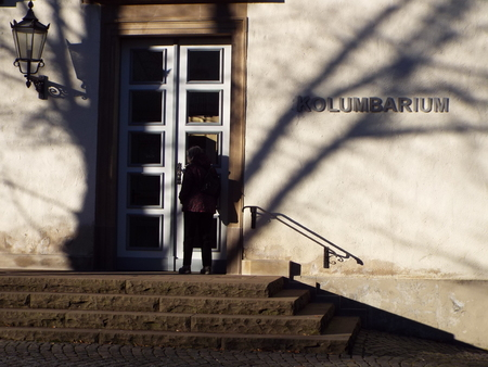 Columbarium - A woman stands in the shade of trees at the door of a columbarium and looks inside. Germany, Hueckeswagen 04/12/2016