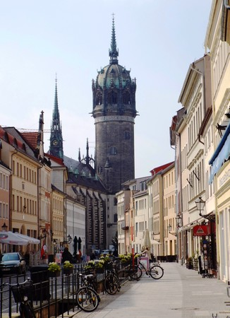 reformation: Castle Street in the old town of Wittenberg; in the background the tower of the Castle Church of All Saints, Wittenberg, Germany 04.12.2016 - At the door of the Castle Church in Wittenberg reformer Martin Luther nailed his 95 theses. By Luther and Melanch