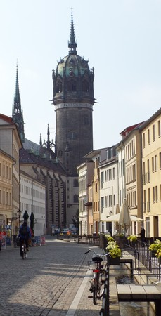 Castle Street in the old town of Wittenberg; in the background the tower of the Castle Church of All Saints, Wittenberg, Germany 04.12.2016 - At the door of the Castle Church in Wittenberg reformer Martin Luther nailed his 95 theses. By Luther and Melanch