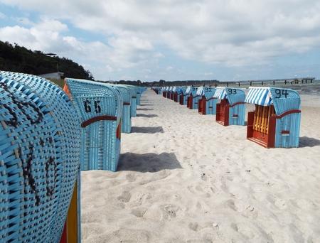 Preseason at the Baltic Sea - Blue beach baskets on the beach under a slightly cloudy sky.