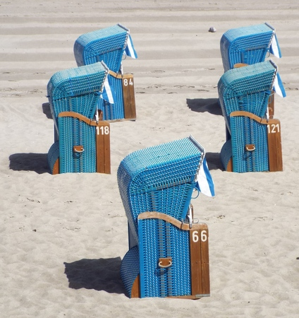 Preseason at the Baltic Sea - Some blue beach baskets in beach sand in side view.