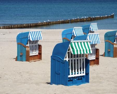 Preseason at the Baltic Sea - Some blue beach baskets in sand beach. Behind it a wooden beam running into the blue sea. Standard-Bild