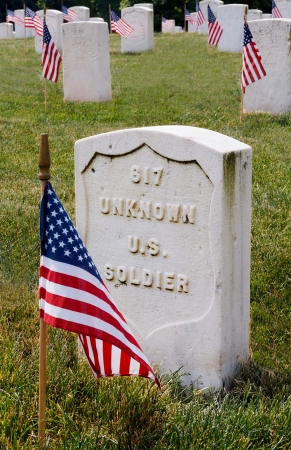The grave of an unknown US soldier marked with  a flag on Memorial Day