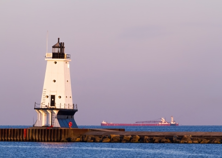 ludington: A large ship passes behind the North Breakwater Light just after sunrise in Ludington, Michigan  Stock Photo