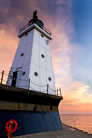 The setting sun provides a dramatically colorful backdrop to the metal clad Ludington North Breakwater Lighthouse in Ludington Michigan  Stock Photo - 14488223