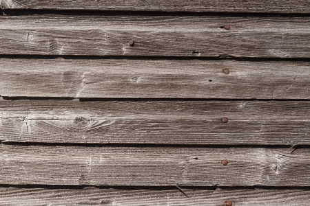 Weathered, graying wood siding with rusty nail heads