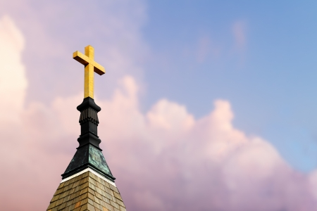 Cross atop a steeple with colorful clouds behind photo