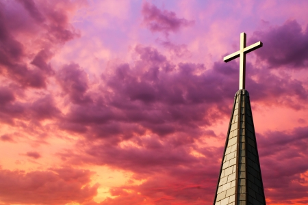 spire: Colorful sunset sky backs a gleaming golden cross high atop a church steeple Stock Photo