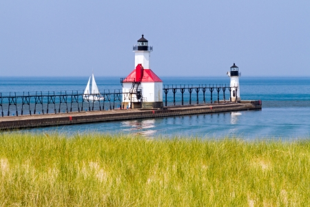 St. Joseph, Michigan North Piewr LIghthouses with a Sailboat on Lake Michigan. photo