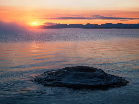 The sun rises over the Absaroka Mountains with The Fishing Cone, a thermal feature of Yellowstone Lake in the foreground photo