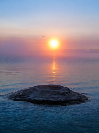 The sun rises over The Fishing Cone, a thermal feature in Yellowstone Lake  photo