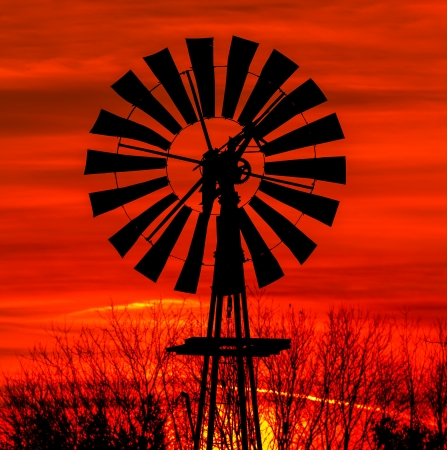 farm equipment: Antique windmill silhouetted by a colorful orange sky  Stock Photo