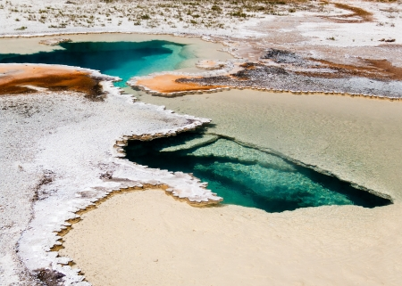 A steaming spring of geotermally-heated water with colorful depoists and thermophiles in Yellowstone photo