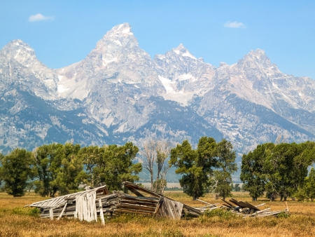 A fallen barn on Mormon Row with the Cathedral Group of the Teton Range in the Antelope Flats area of Grand Teton National Park, Wyoming photo
