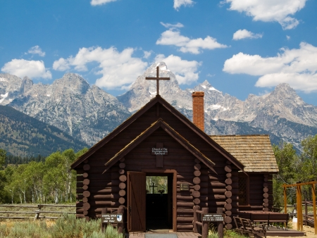 The Chapel of the Transfiguration is a small log church built with a window behind the altar to frame the Cathedral Group of Wyoming