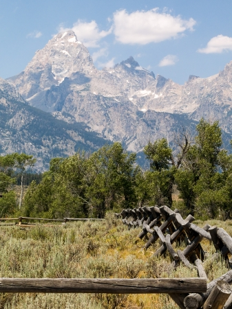 A rustic fence leads to the peaks of the Cathedral Group of the Teton Mountain Range in Grand Teton National Park, Wyoming, USA Stock Photo - 18659227