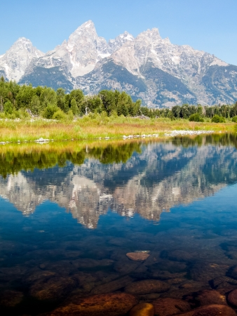 The Cathedral Group of the Teton Mountain Range is reflected on the waters of the Snake River at Schwabacher;s Landing in Grand Teton National Park, Wyoming, USA. photo