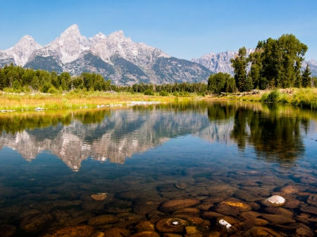 The Teton Mountain Range is reflected in the shallow and still waters of a braid of the Snake River in Grand Teton National park, Wyoming, USA Stock Photo