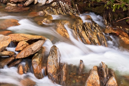swiftly: Water flows swiftly over a stream Stock Photo