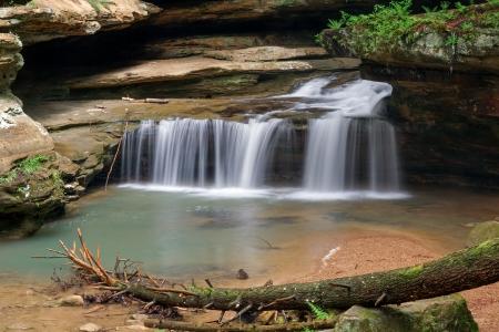 오하이오 주 Hocking Hills 주립 공원의 Old Man 's Cave에서 중간 폭포 마지막까지 물이 뚝뚝 떨어지고 포 그라운드에서 큰 나무가 떨어졌습니다. 스톡 콘텐츠