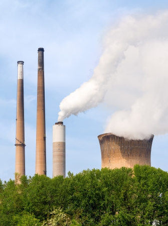 Smoke and steam billow above smokestacks and a cooling tower at a coal-fired power plant. Stock Photo
